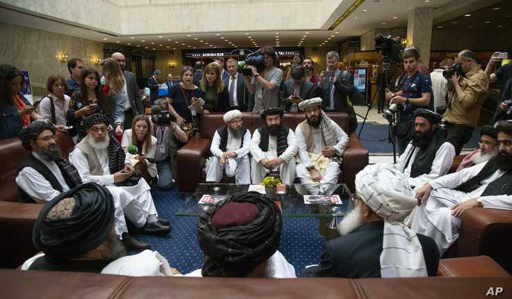 Mullah Abdul Ghani Baradar, the Taliban group's top political leader, (L), Sher Mohammad Abbas Stanikzai, the Taliban's chief negotiator, second left, and other members of the Taliban delegation speak to reporters before talks in Moscow, May 28, 2019.