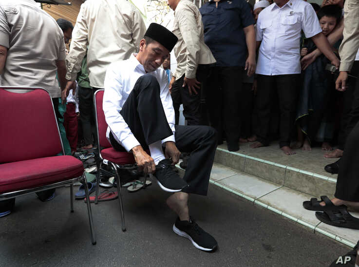 Indonesian President Joko Widodo put his sneakers back on after attending a Friday prayer at a mosque in Jakarta, Indonesia, July 26, 2019.