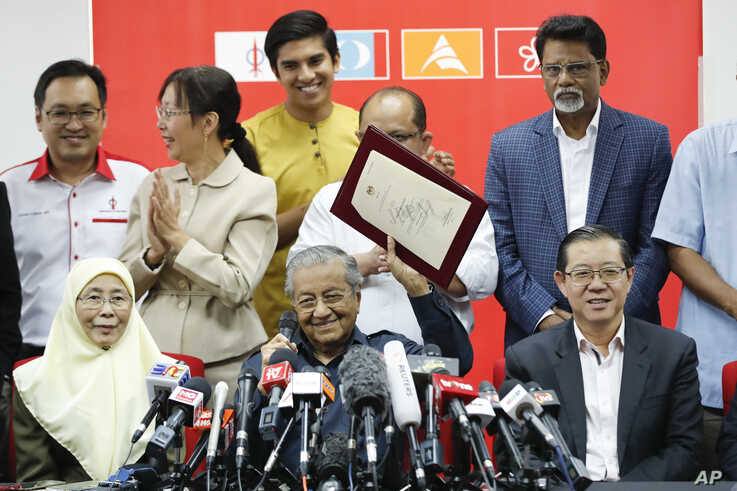 """Malaysia Prime Minister Mahathir Mohamad, center, shows document of Registration of Pakatan Harapan """"Alliance of Hope"""" during a press conference in Petaling Jaya, Malaysia on Thursday, May 17, 2018. Mahathir, who was prime minister for 22 years…"""
