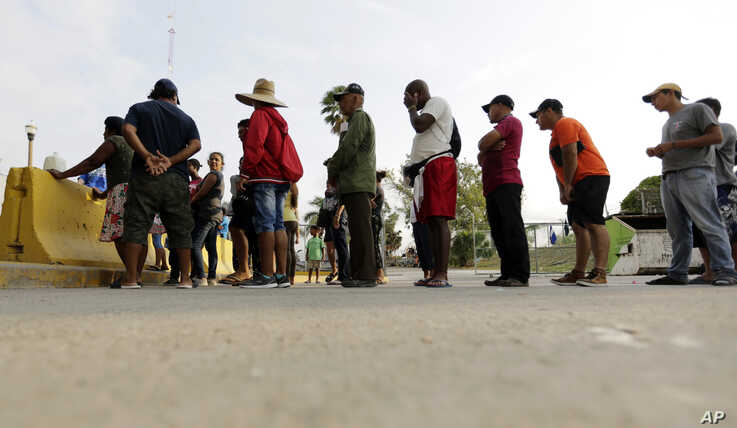 FILE - In this April 30, 2019, file photo, migrants seeking asylum in the United States line up for a meal provided by volunteers near the international bridge in Matamoros, Mexico. The U.S. government will expand its policy requiring asylum seekers…