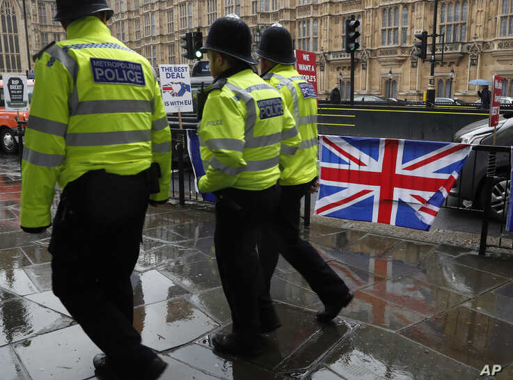 Three policemen patrol past various Brexit flags and banners outside the Houses of Parliament in London, Tuesday, April 2, 2019.  Britain's Prime Minister Theresa May is set for long Cabinet meeting Tuesday, as the government tries to find a way out…
