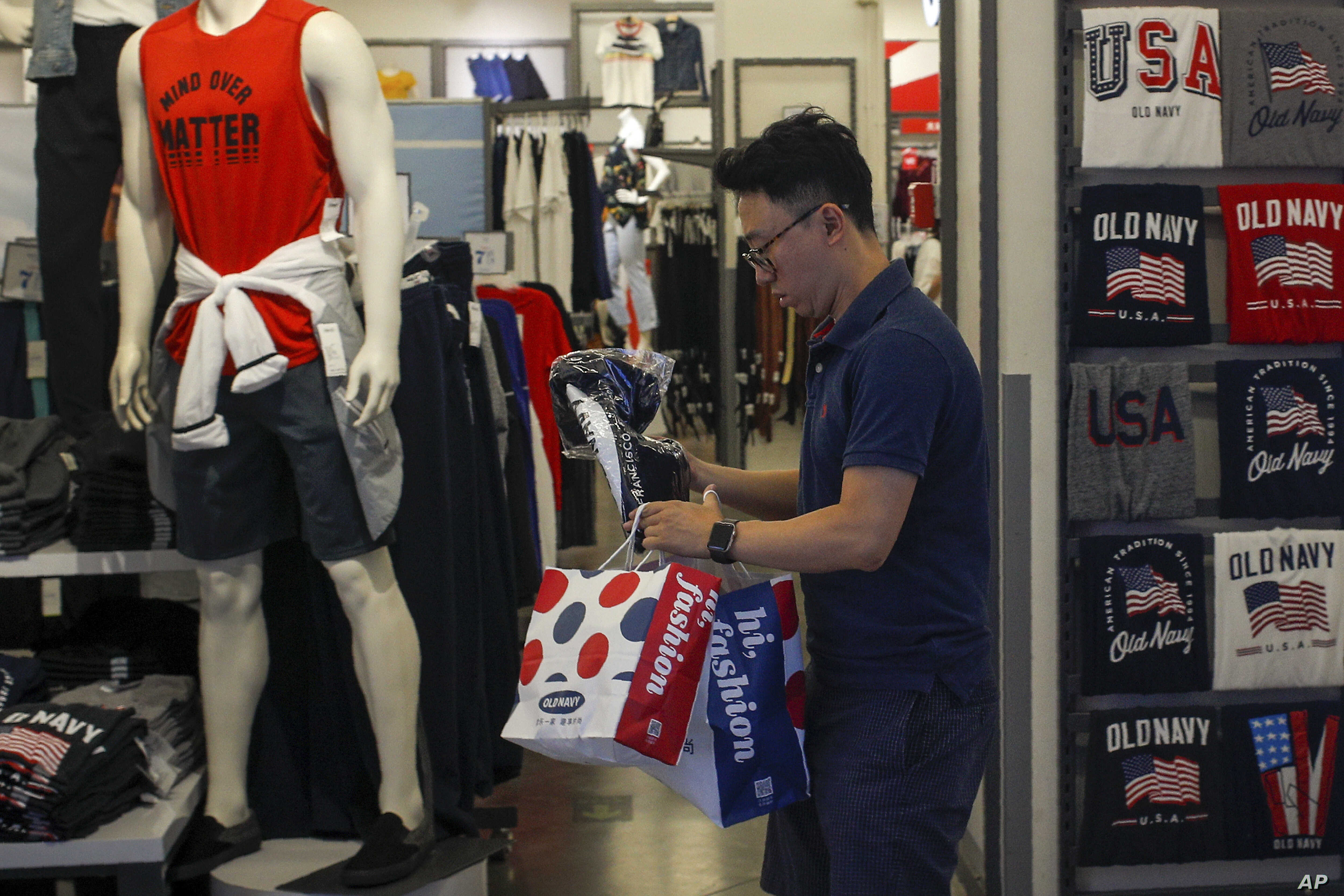 A man buys clothes from an American clothing store having a promotion sale at a shopping mall in Beijing, Monday, July 15, 2019. China's economic growth sank to its lowest level in at least 26 years in the quarter ending in June, adding to pressure…