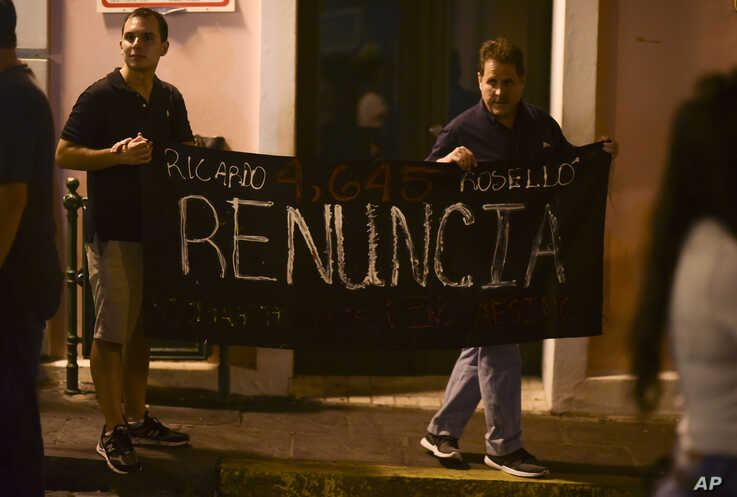 "Citizens carry a banner that reads ""Ricardo Rosello, renounce"" during a protest denouncing a wave of arrests for corruption that has shaken the country and demanding Gov. Ricardo Rosello resign, in San Juan, Puerto Rico, July 11, 2019."