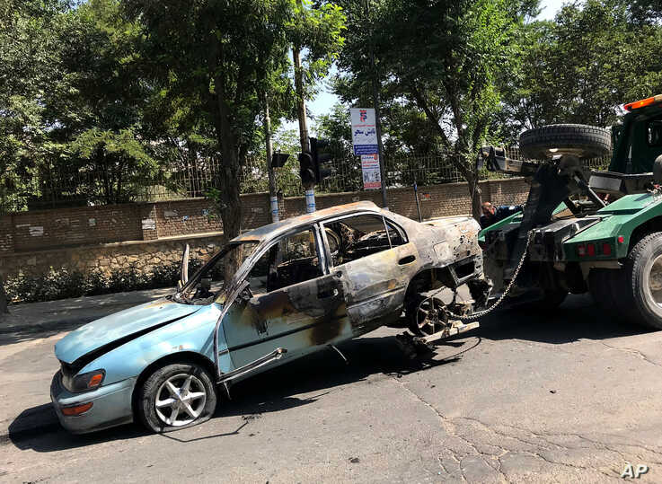 A damaged car is towed away from the site of an explosion in Kabul, Afghanistan, July 19, 2019.