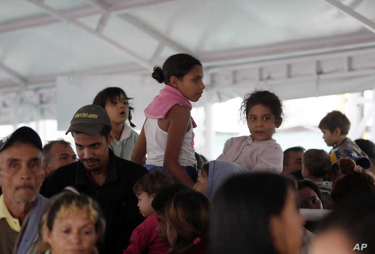 Venezuelans wait at an immigration processing office on the Rumichaca bridge, before crossing the border from Colombia to Ecuador, Thursday, June 13, 2019. Venezuelan migrants are making their way to Peru, where on June 15, the country will start…