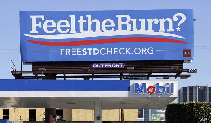 FILE - A billboard above a gas station, April 1, 2016, promotes testing for sexually transmitted diseases. The number of cases of STDs - chlamydia, gonorrhea and syphilis - in California reached a record high in 2017.