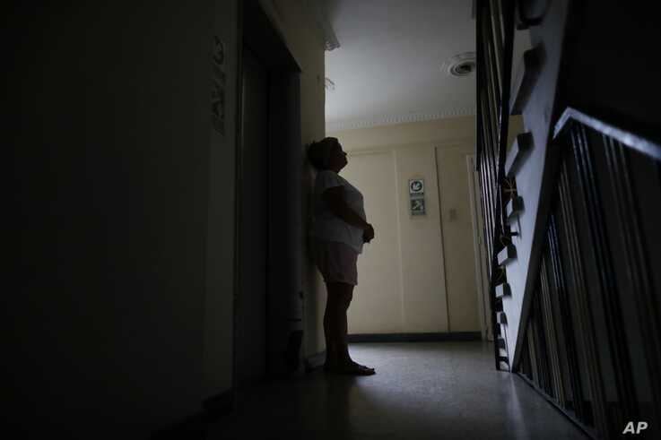 Orelis Lehmann rests from climbing the stairs to her apartment in Caracas, Venezuela, Tuesday, July 23, 2019. With the power outage that began Monday afternoon the elevator is out. (AP Photo/Ariana Cubillos)