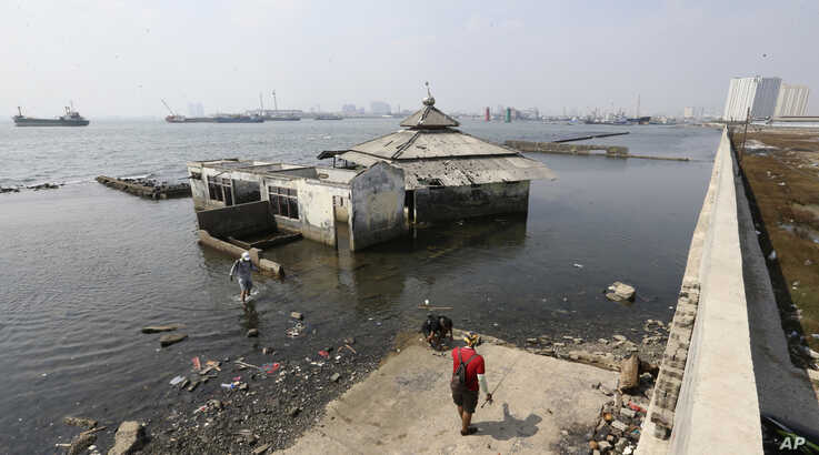 People walk near a giant sea wall that prevents sea water from flowing into Jakarta, Indonesia, July 27, 2019.