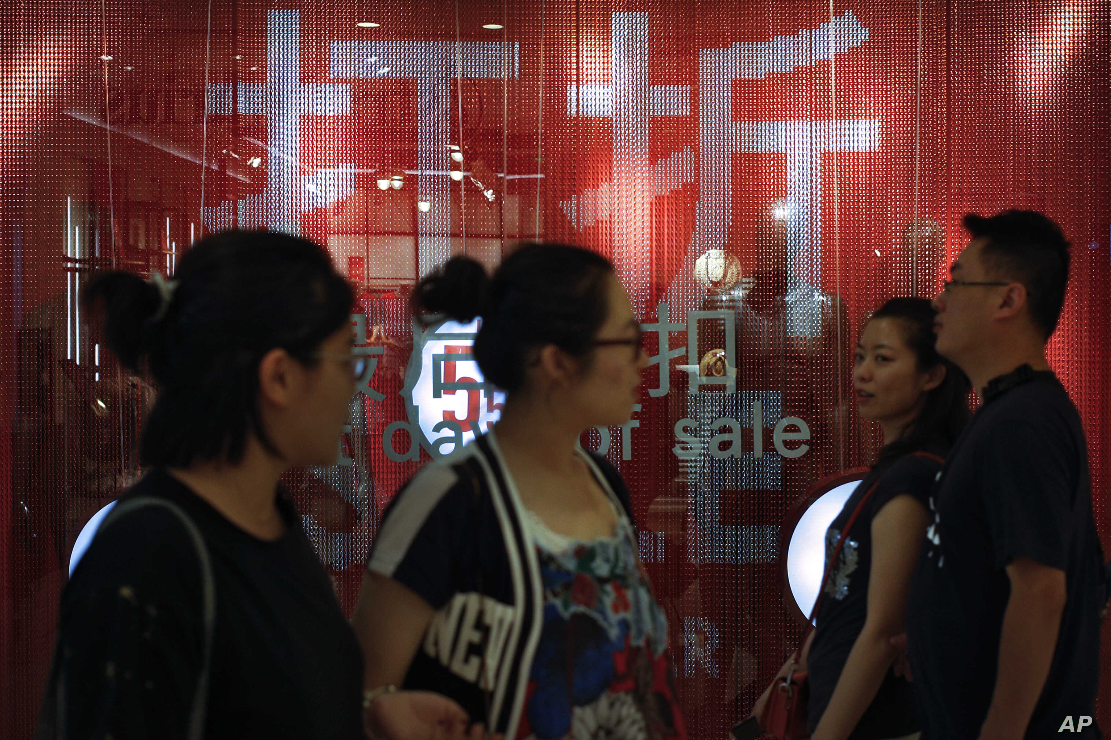 People walk by a fashion retailer having promotion sale at a shopping mall in Beijing, Monday, July 15, 2019. China's economic growth sank to its lowest level in at least 26 years in the quarter ending in June, adding to pressure on Chinese leaders…