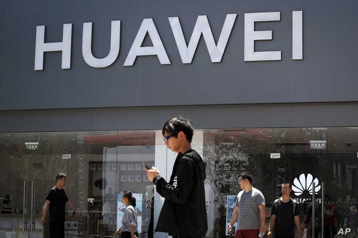People walk past a Huawei retail store in Beijing, Sunday, June 30, 2019. Once again, Presidents Donald Trump and Xi Jinping have hit the reset button in trade talks between the world's two biggest economies, at least delaying an escalation in…
