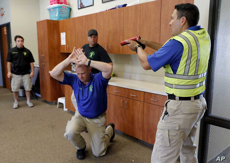 Police officers David Riggall, kneeling, and Nick Guadarrama, right, instruct students Bryan Hetherington, left rear, and Chris Scott, center rear, during a security training session at Fellowship of the Parks campus in Haslet, Texas, July 21, 2019.