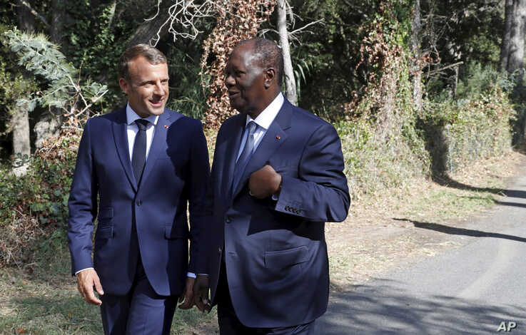 French President Emmanuel Macron, left, talks with Ivory Coast's President Alassane Ouattara during a ceremony marking the 75th anniversary of the WWII Allied landings in Provence, in Saint-Raphael, southern France, Thursday, Aug. 15, 2019.