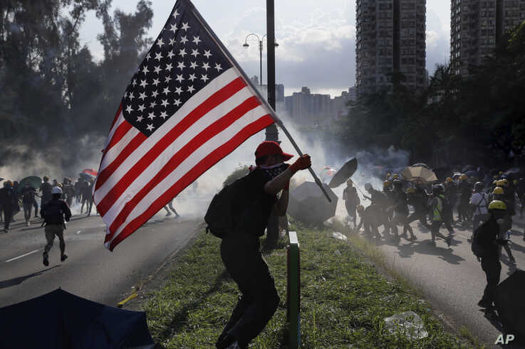 FILE - A protester runs with a United States flag as tear gas is released on protesters in Hong Kong, Aug. 5, 2019.