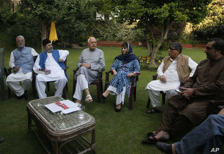 Former Jammu and Kashmir Chief Minister Mehbooba Mufti, fourth left, National Conference president Farooq Abdullah, third left and other leaders sit during an all parties meeting in Srinagar, India, Sunday, Aug. 4, 2019. (AP Photo/Mukhtar Khan)