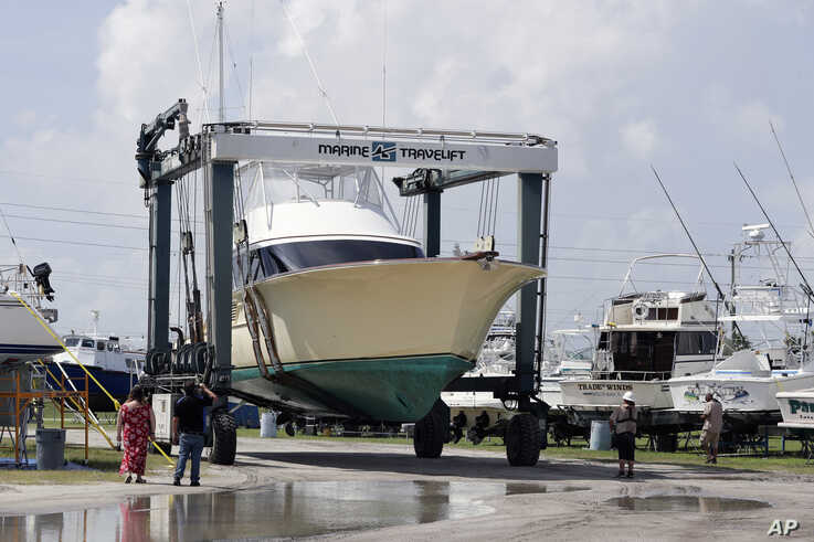 A large boat is moved to a storage lot on dry land at a marina in Cape Canaveral, Fla. as boat owners prepare for the arrival of Hurricane Dorian Saturday, Aug. 31, 2019, The latest forecast says Dorian is expected to stay just off shore of Florida…
