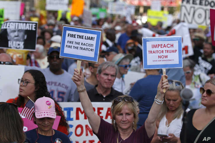 "Protesters hold signs during a ""We Stand Up"" gathering, protesting a rally by President Donald Trump, Thursday, Aug. 1, 2019, in Cincinnati. (AP Photo/Gary Landers)"