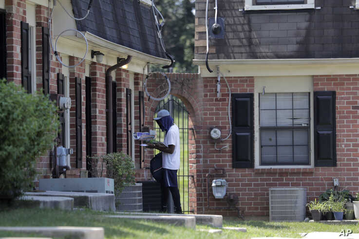 A mail carrier delivers mail at a home at the Dutch Village apartments, July 30, 2019, in Baltimore. The apartment complex is owned by Jared Kushner, son-in-law of President Donald Trump.