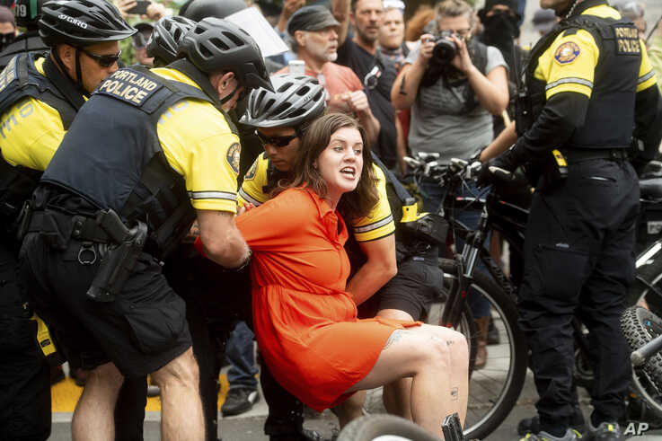 "Police officers detain a protester against right-wing demonstrators following an ""End Domestic Terrorism"" rally in Portland, Ore., on Saturday, Aug. 17, 2019. Although the main protest remained largely peaceful, some skirmishes erupted in the…"