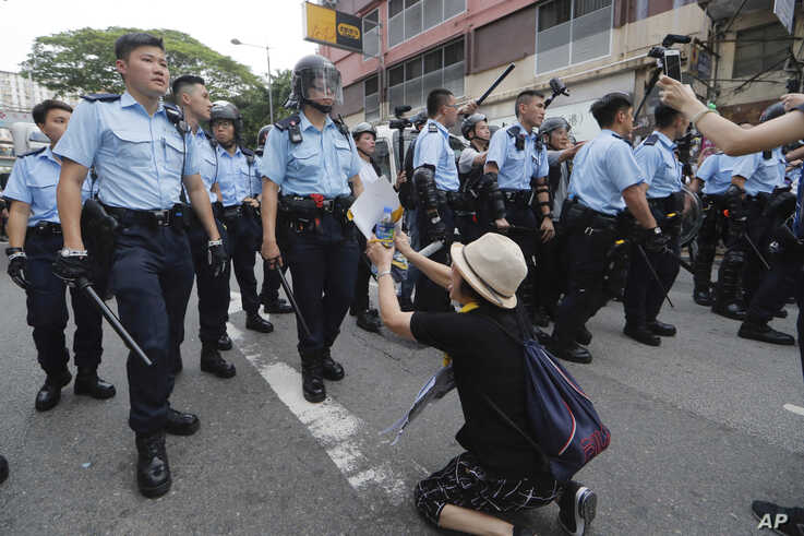 FILE - A supporter begs police not to attack protesters in Hong Kong, July 31, 2019.