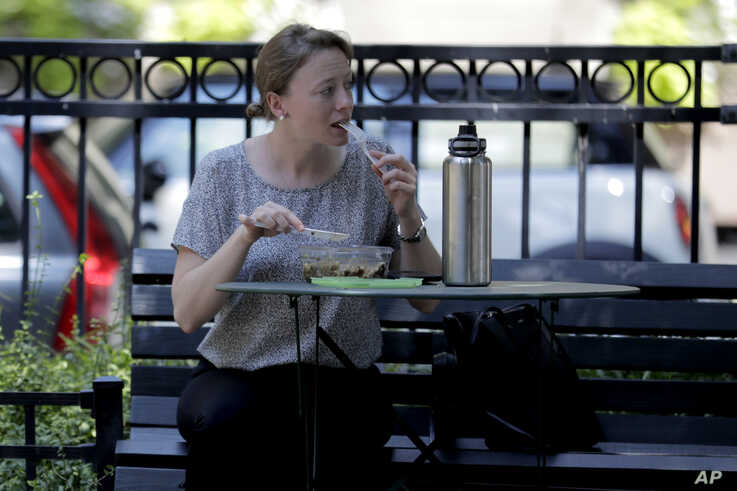 A woman enjoys lunch at the Mount Vernon Place Square in the Mount Vernon section of Baltimore, July 29, 2019.
