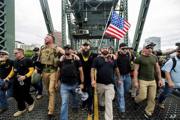 "Members of the Proud Boys and other right-wing demonstrators march across the Hawthorne Bridge during an ""End Domestic Terrorism"" rally in Portland, Ore., on Saturday, Aug. 17, 2019. The group includes organizer Joe Biggs, in green hat, and Proud…"