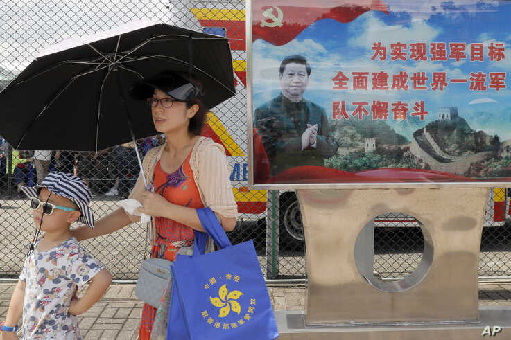 FILE - Visitors walk past a poster featuring Chinese President Xi Jinping during an open day of Stonecutter Island naval base, in Hong Kong to mark the 22nd anniversary of Hong Kong handover to China, June 30, 2019