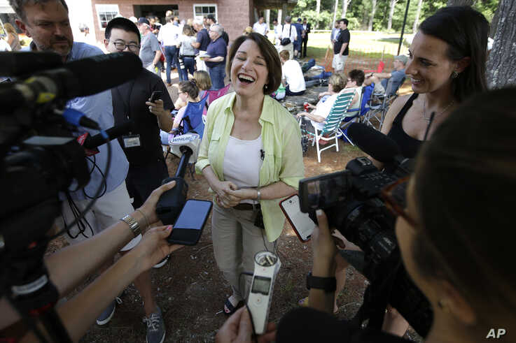 Democratic presidential candidate Sen. Amy Klobuchar, D-Minn., center, laughs while speaking with reporters, Sunday, Aug. 18, 2019, at the Hillsborough County Democrats Summer Picnic, in Greenfield, N.H. (AP Photo/Steven Senne)