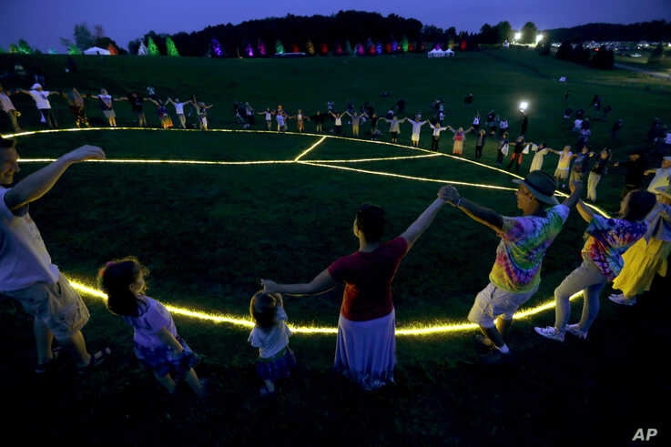 People hold hands in a circle around a large, illuminated peace sign on the original site of the 1969 Woodstock Music and Arts Fair in Bethel, N.Y., Aug. 15, 2019.