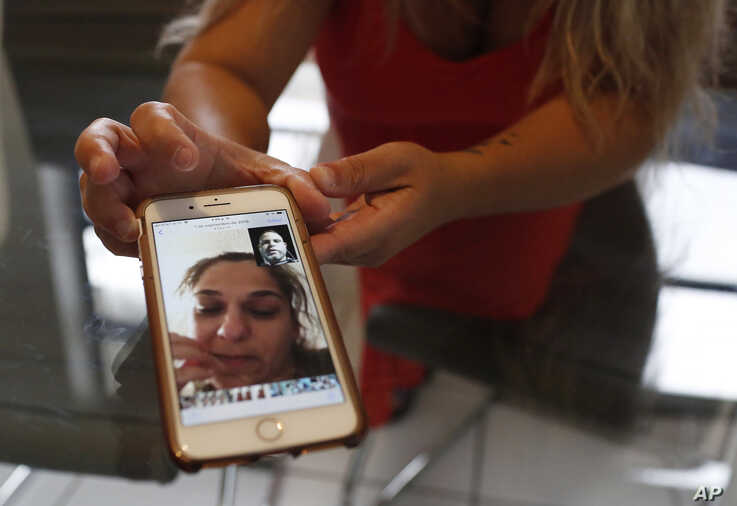 In this Aug. 6, 2019, photo, Barbara Rodriguez shows a photograph on her phone of her talking to her husband, Pablo Sanchez at…
