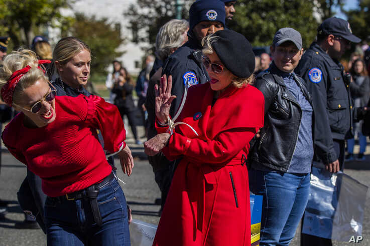Actress Jane Fonda, center, gives fellow activist a high five after they were arrested during a rally on Capitol Hill in…
