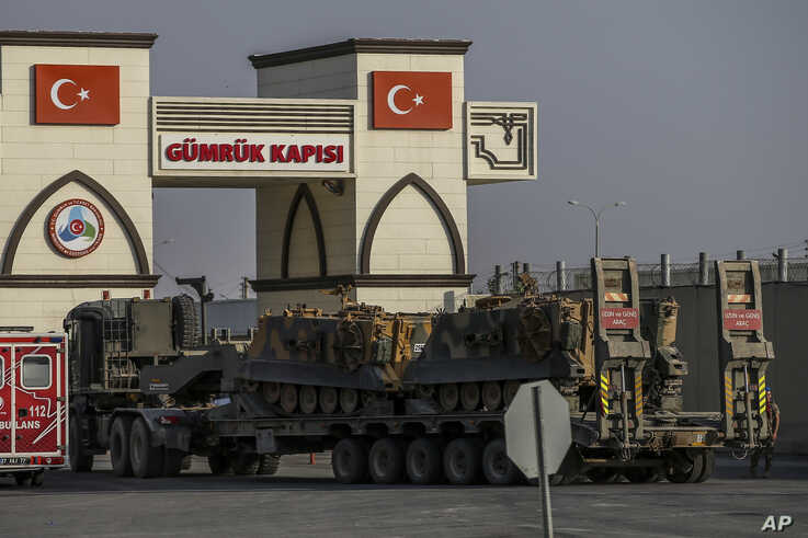 A Turkish forces truck transporting armoured personnel carriers, crosses the border with Syria in Karkamis, Gaziantep province,…