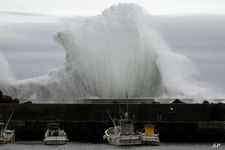 Men look at fishing boats as surging waves hit against the breakwater while Typhoon Hagibis approaches at a port in town of…