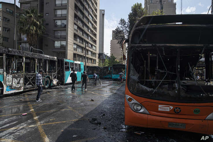 Buses that were set alight by demonstrators during last night's protests stand on a street in Santiago, Chile, Saturday, Oct…