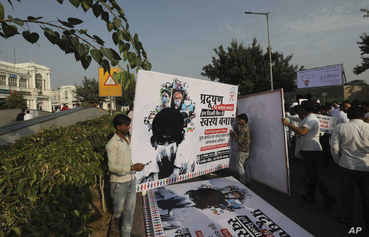 Congress party volunteers put up banners along the road for a march protesting against the alarming levels of pollution in the…