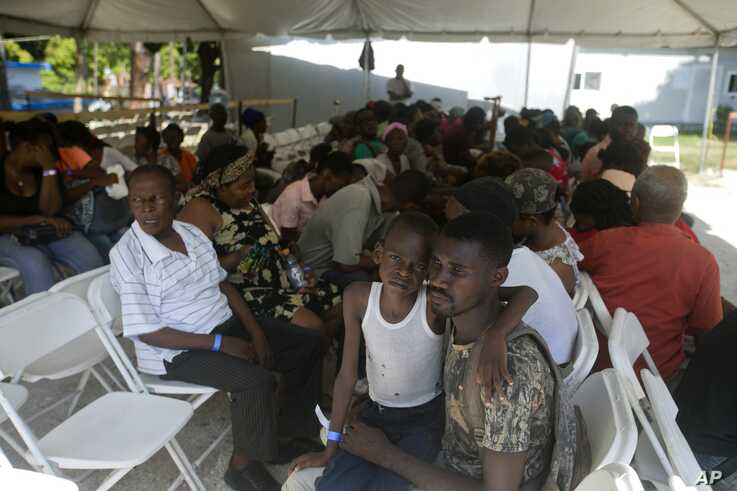 Patients wait under a tarp to see a doctor from the U.S. Navy hospital ship USNS Comfort anchored off Port-au-Prince, Haiti,…