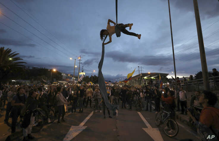 A man performs hanging from a bridge during an anti-government protest in Bogota, Colombia, Wednesday, Nov. 27, 2019…