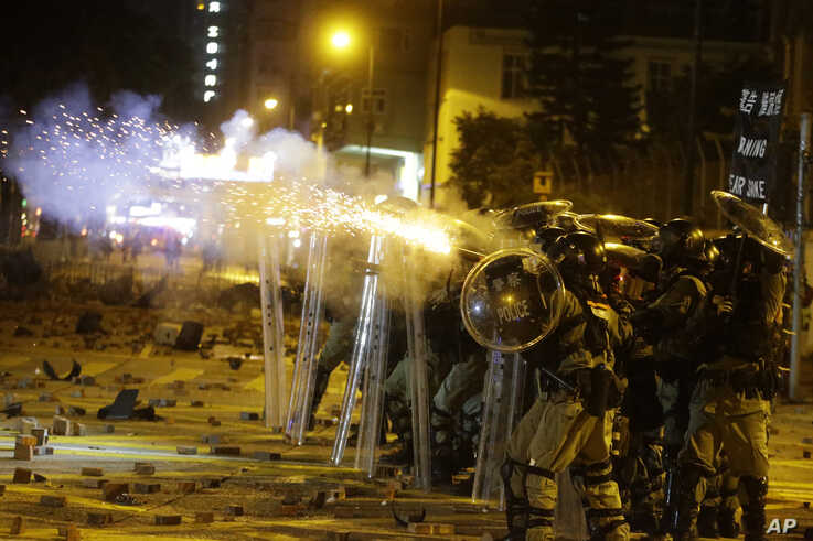Police in riot gear fire tear gas at protestors near the Hong Kong Polytechnic University in Hong Kong on Saturday, Nov. 16,…