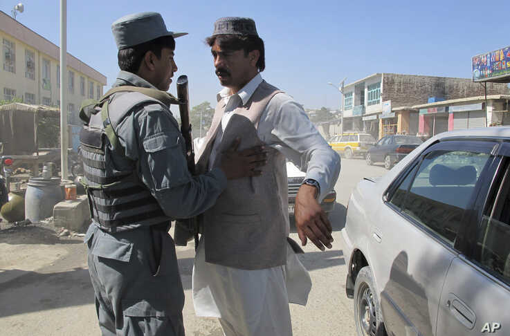 An Afghan policeman body checks a man in Khost, Afghanistan, Sunday Oct. 2, 2011. Security measures are tight after the…