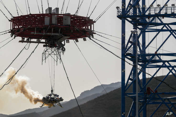A lander is lifted during a test of hovering, obstacle avoidance and deceleration capabilities at a facility in Huailai in…
