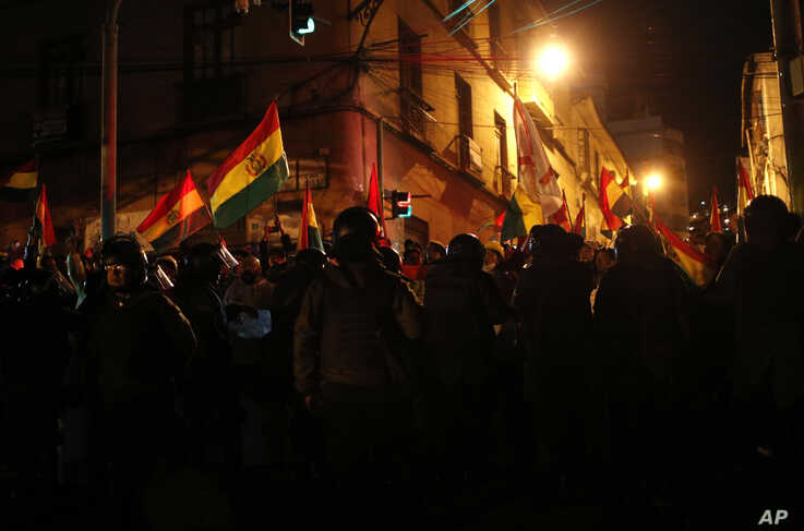 A cordon of police block demonstrators from reaching the government palace during a protest against President Evo Morales'…