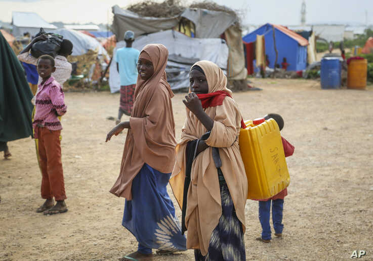 In this photo taken Monday, Nov. 4, 2019, children displaced by recent floods reach the outskirts of the town of Beledweyne in…