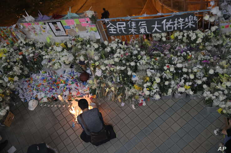 "A protester light candles near flowers and a banner which reads ""From all of us - God bless Chow Tsz-Lok"" at the site where…"