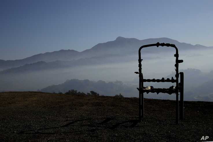 A charred lawn chair overlooks a valley filled with smoke from the Kincade Fire near Healdsburg, Calif., Nov. 1, 2019. (AP…