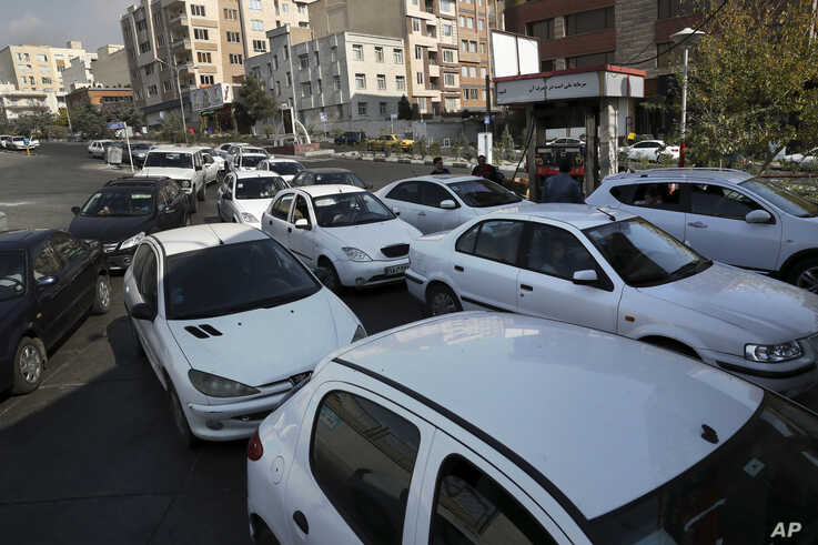 Vehicles queue to enter a gas station in Tehran, Iran, Friday, Nov. 15, 2019. Authorities have imposed rationing and increased…