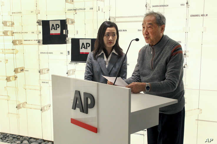 Rao Jian, right, son of Y.C. Jao, speaks during a ceremony at the Associated Press headquarters, in New York, Wednesday, Dec…