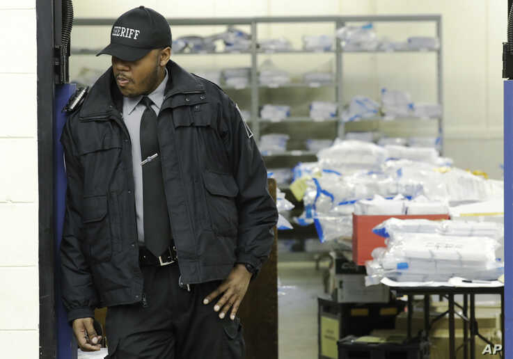 A Milwaukee County sheriff guards a room where ballots are stacked up as a statewide presidential election recount begins…