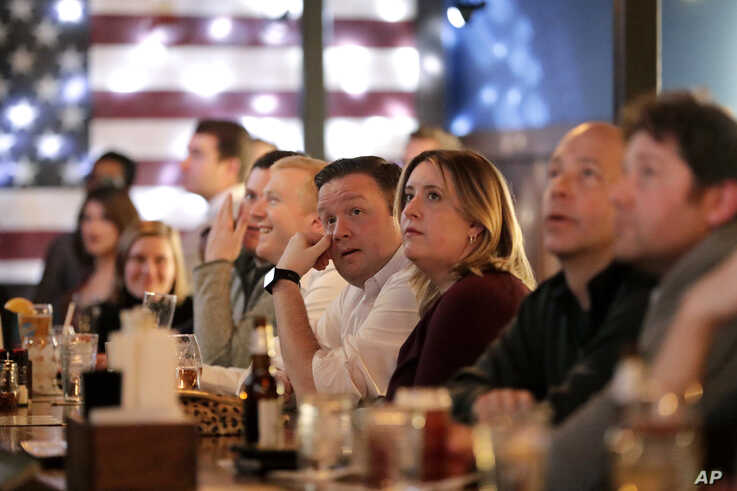 People watch as members of the House of Representatives voting on article one of the impeachment against President Donald Trump…