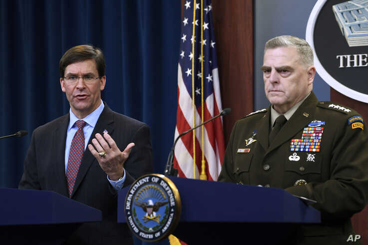 Defense Secretary Mark Esper, left, standing with Joint Chiefs​ Chairman Gen. Mark Milley, right, speaks during a news…