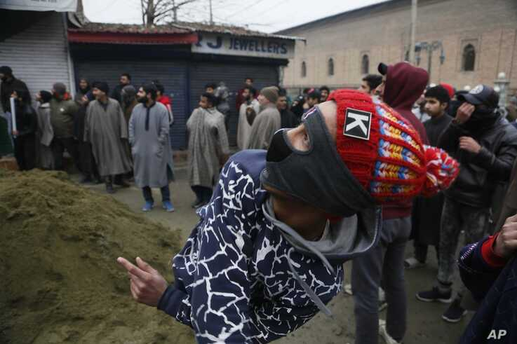 A masked Kashmiri boy throws stones at a police drone flying over Jamia Masjid mosque where Kashmiris are offering their first…