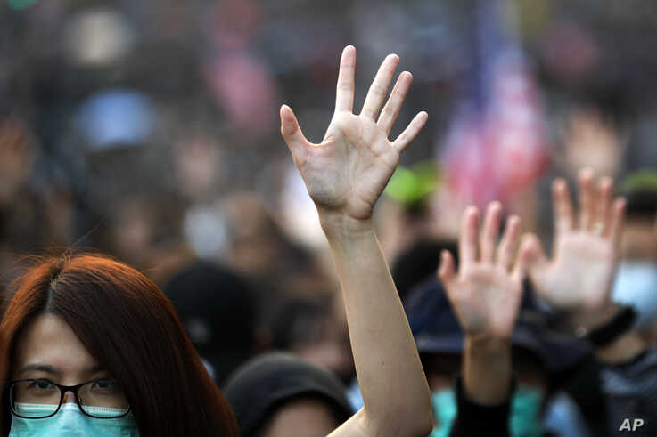 Pro-democracy protesters raise their hands to symbolize the five demands of the pro-democracy movement during a rally in Hong…